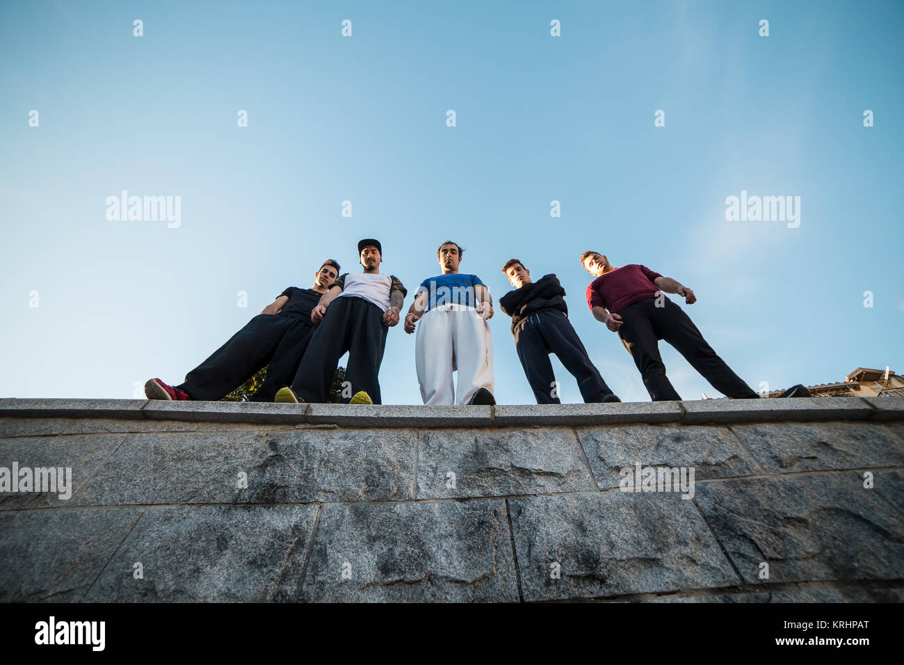From below group of parkour professionals standing and posing on the wall. - Stock Image