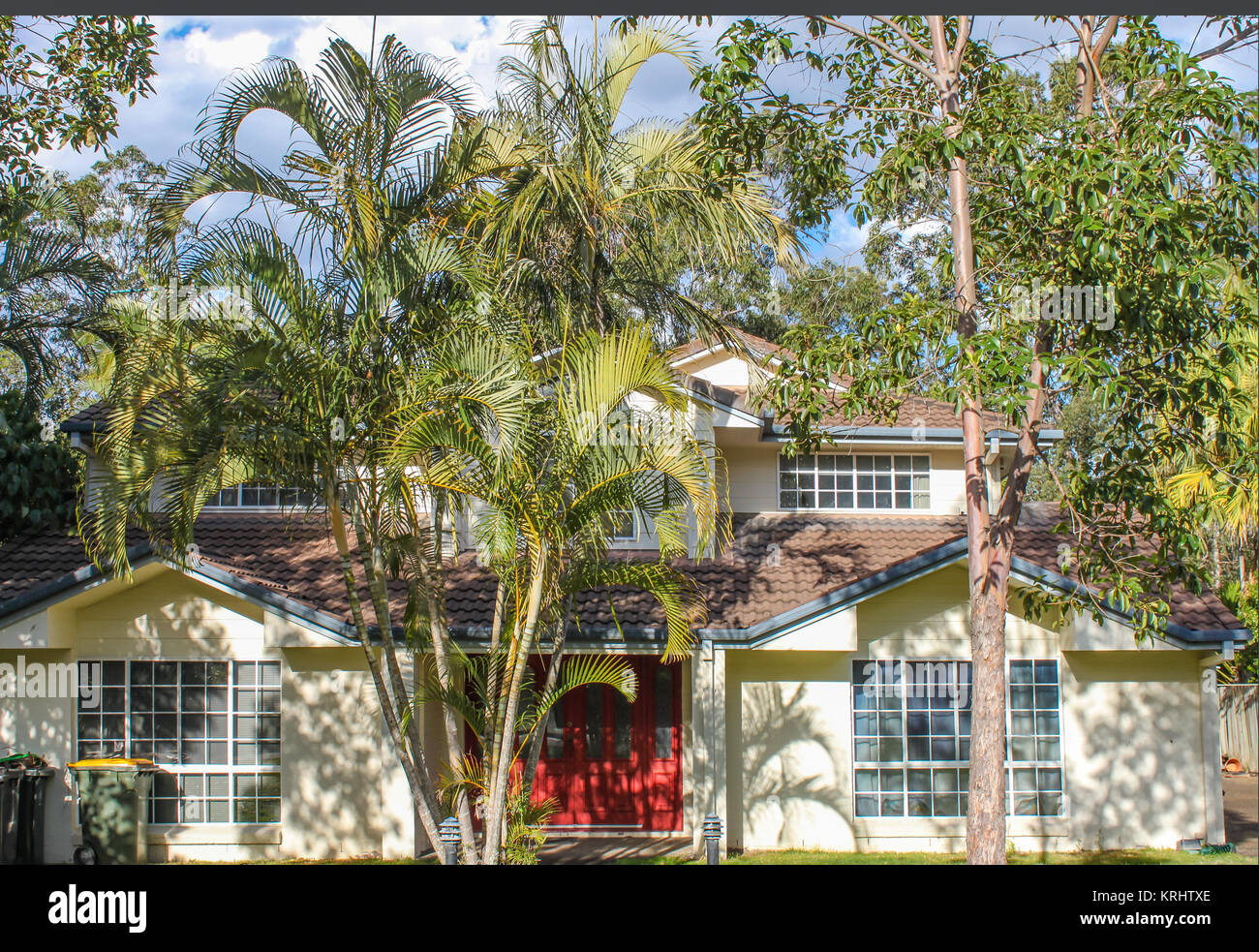 Typical suburban house outside Brisbane Australia with gum trees and palm trees on a beautiful summer day - Stock Image
