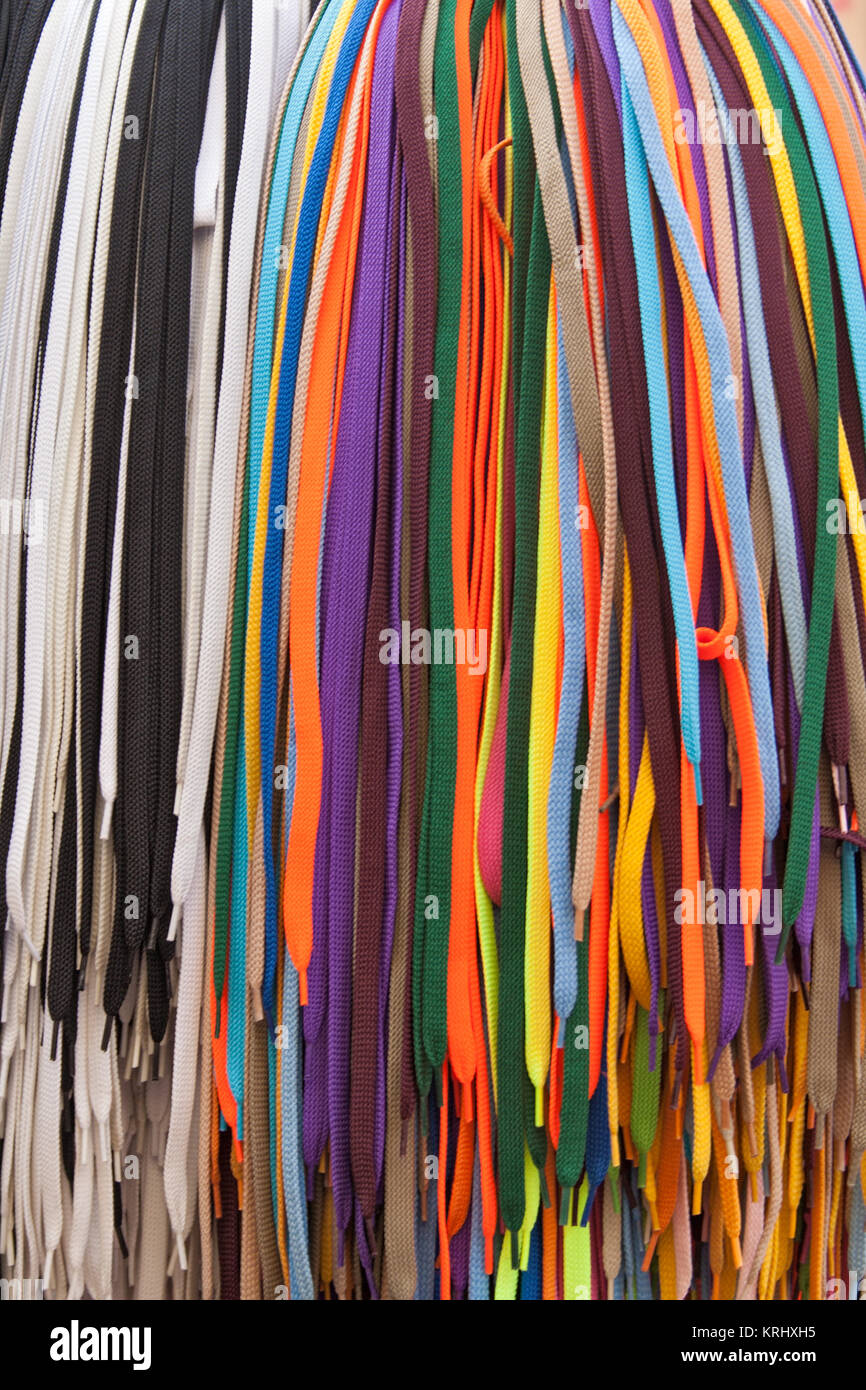Collection of many colorful shoelaces at a retail stand - Stock Image