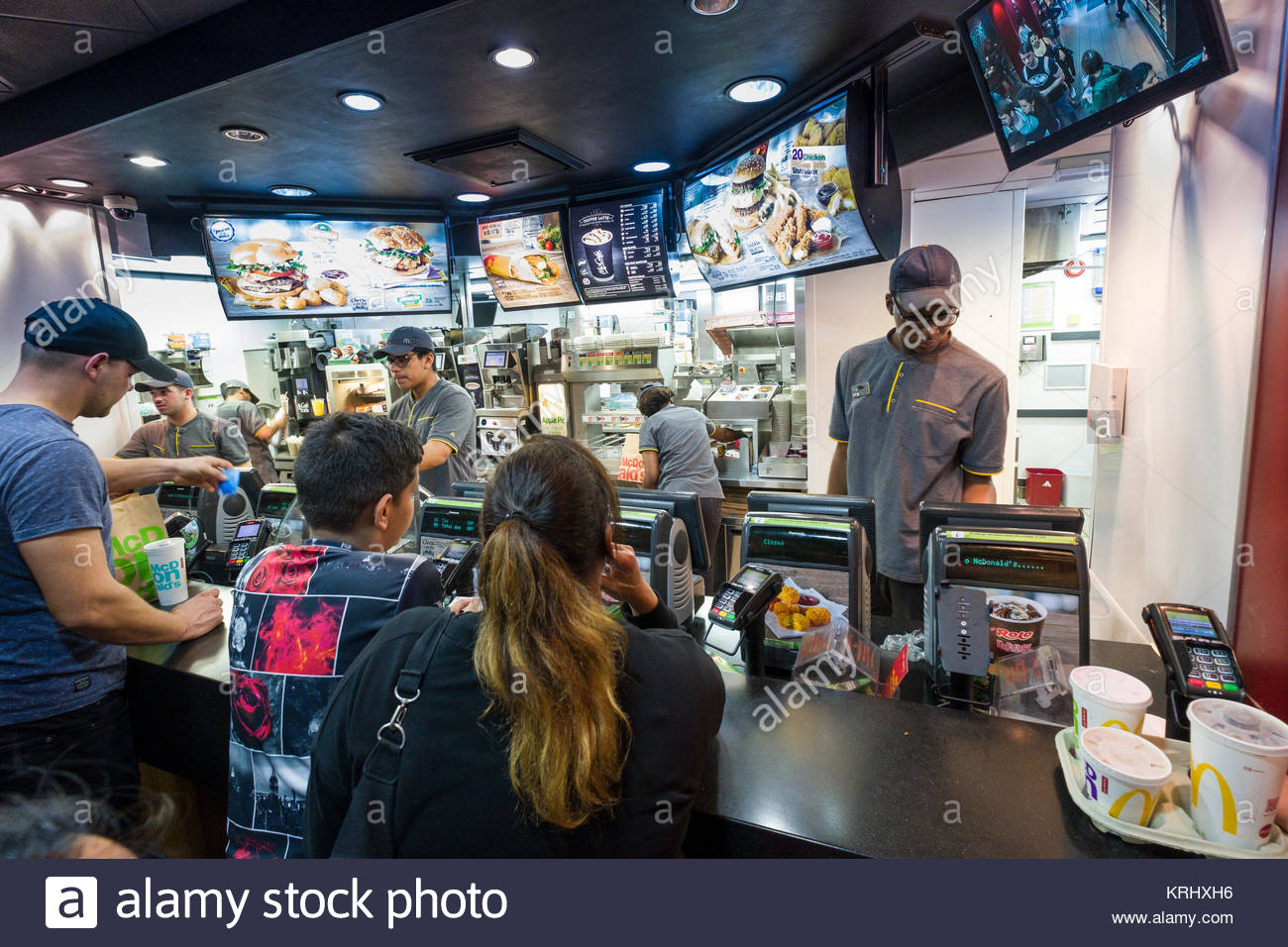 Man working behind the counter at McDonald's fast-food restaurant, London, England, United Kingdom - Stock Image