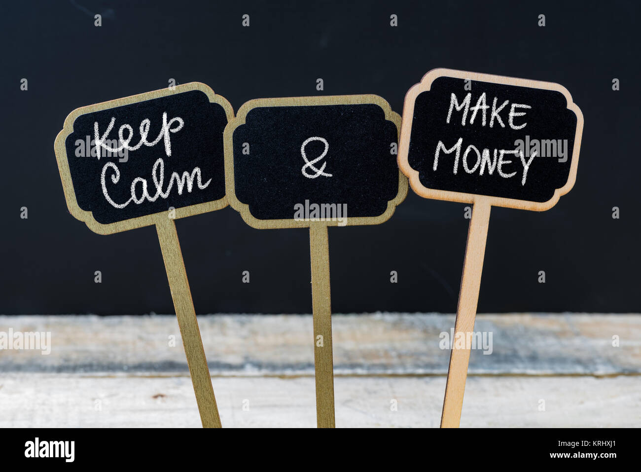 Keep Calm and Make Money message written with chalk on mini blackboard labels - Stock Image