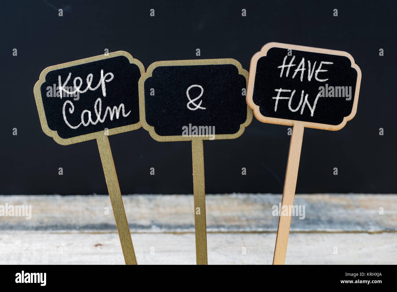 Keep Calm and Have Fun message written with chalk on mini blackboard labels - Stock Image