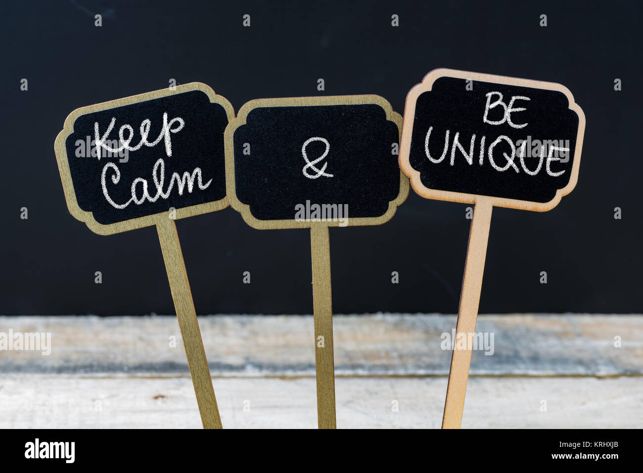 Keep Calm and Be Unique message written with chalk on mini blackboard labels - Stock Image