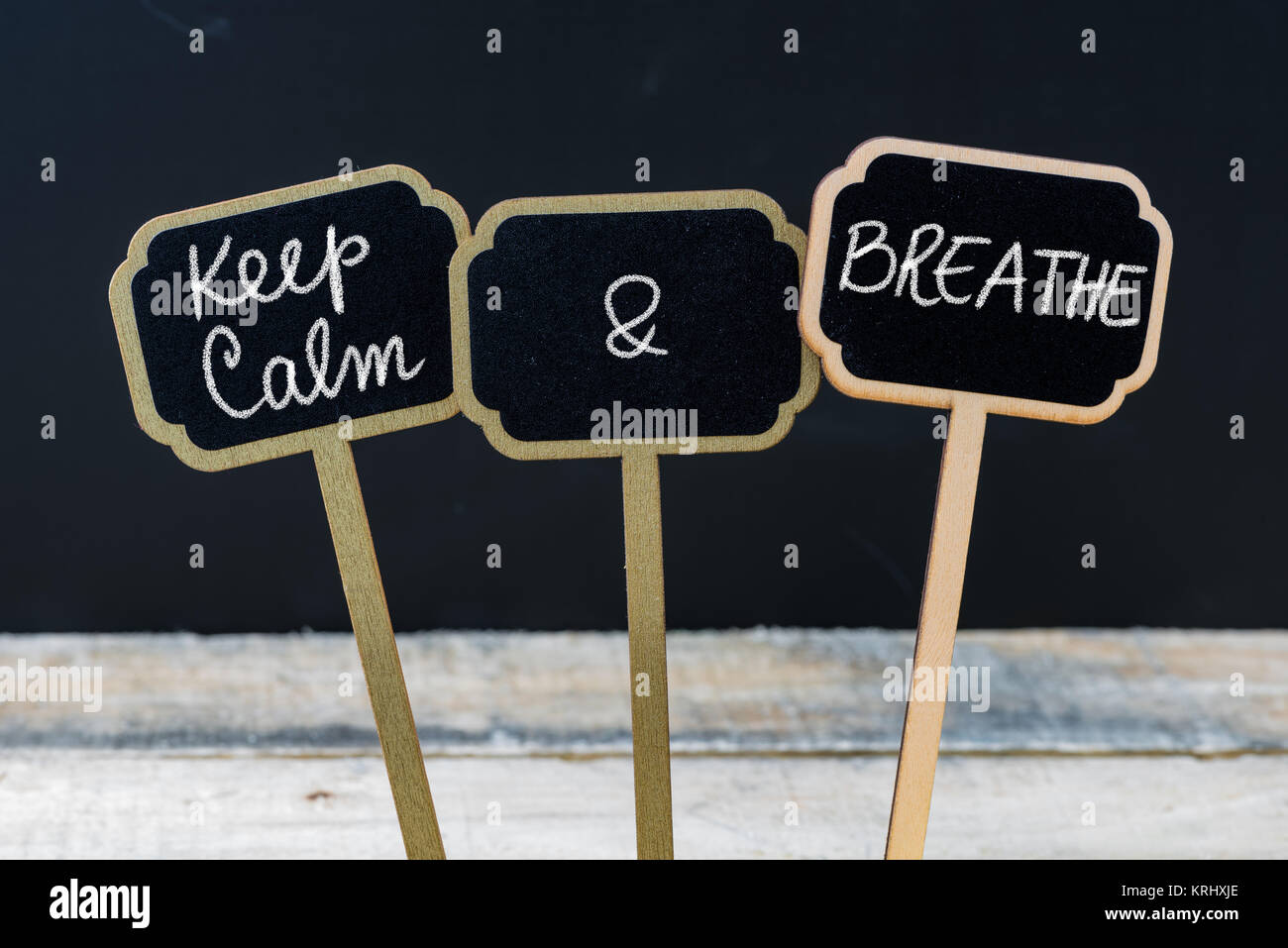 Keep Calm and Breathe message written with chalk on mini blackboard labels - Stock Image