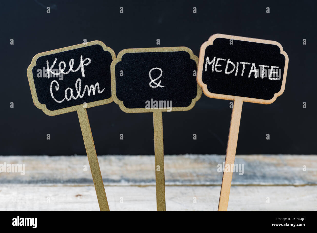 Keep Calm and Meditate message written with chalk on mini blackboard labels - Stock Image