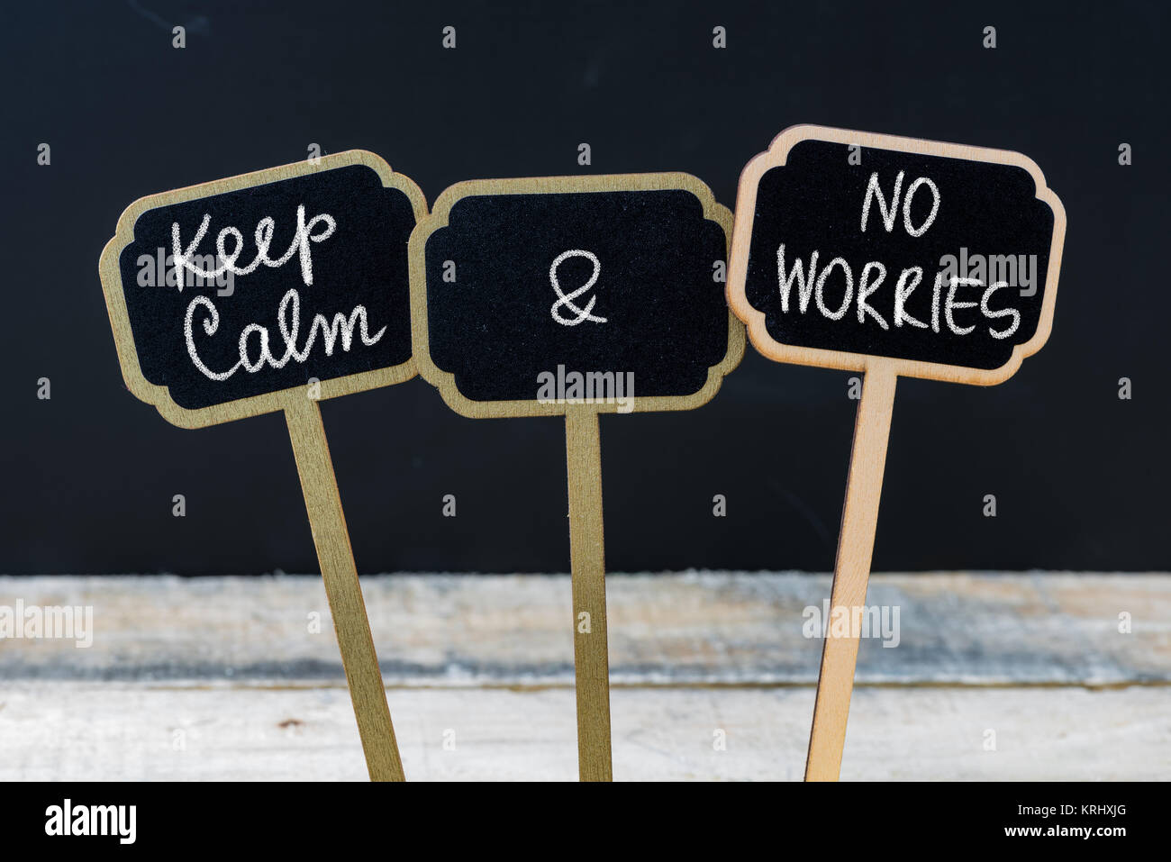 Keep Calm and No Worries message written with chalk on mini blackboard labels - Stock Image