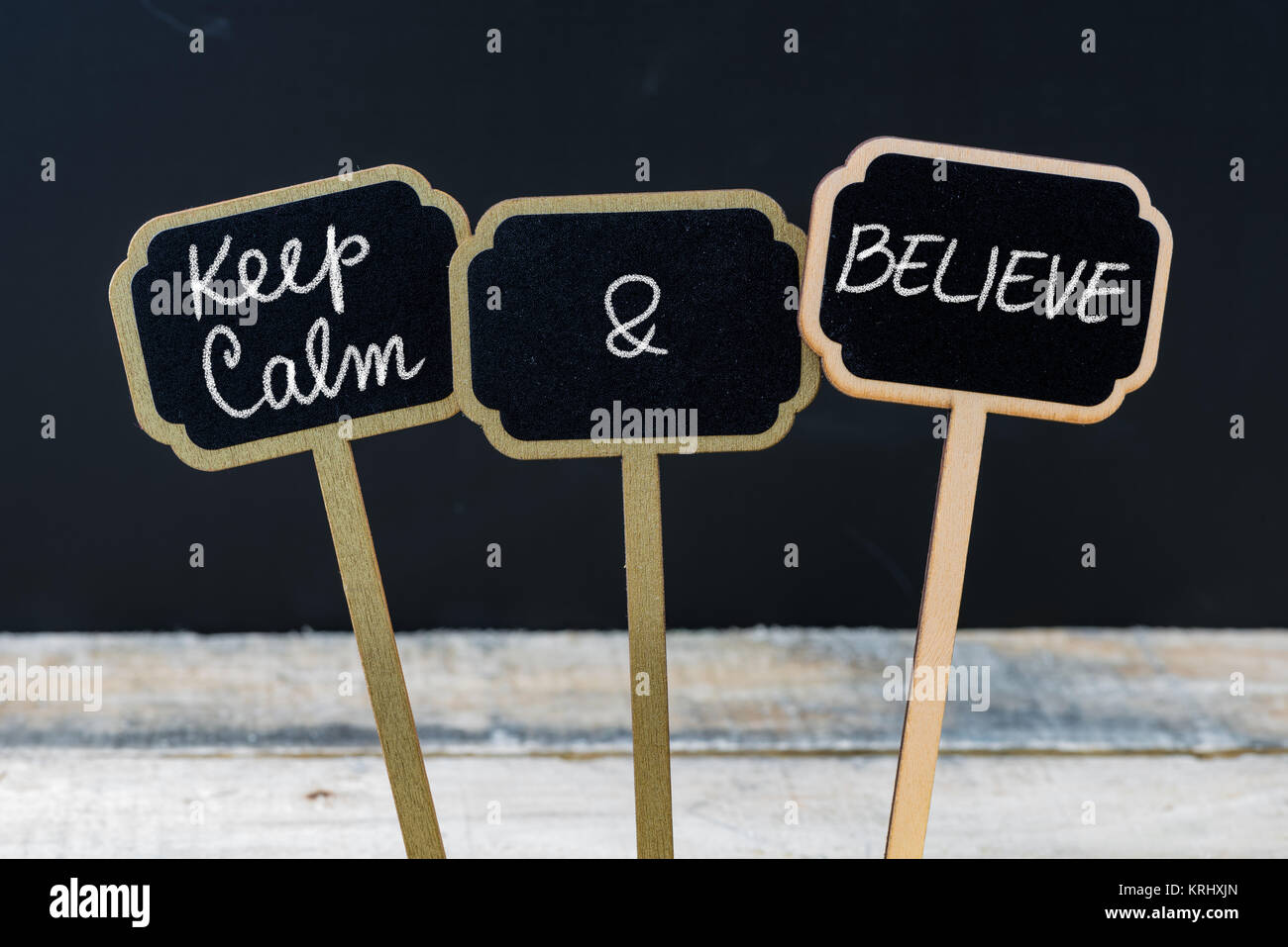 Keep Calm and Believe message written with chalk on mini blackboard labels - Stock Image