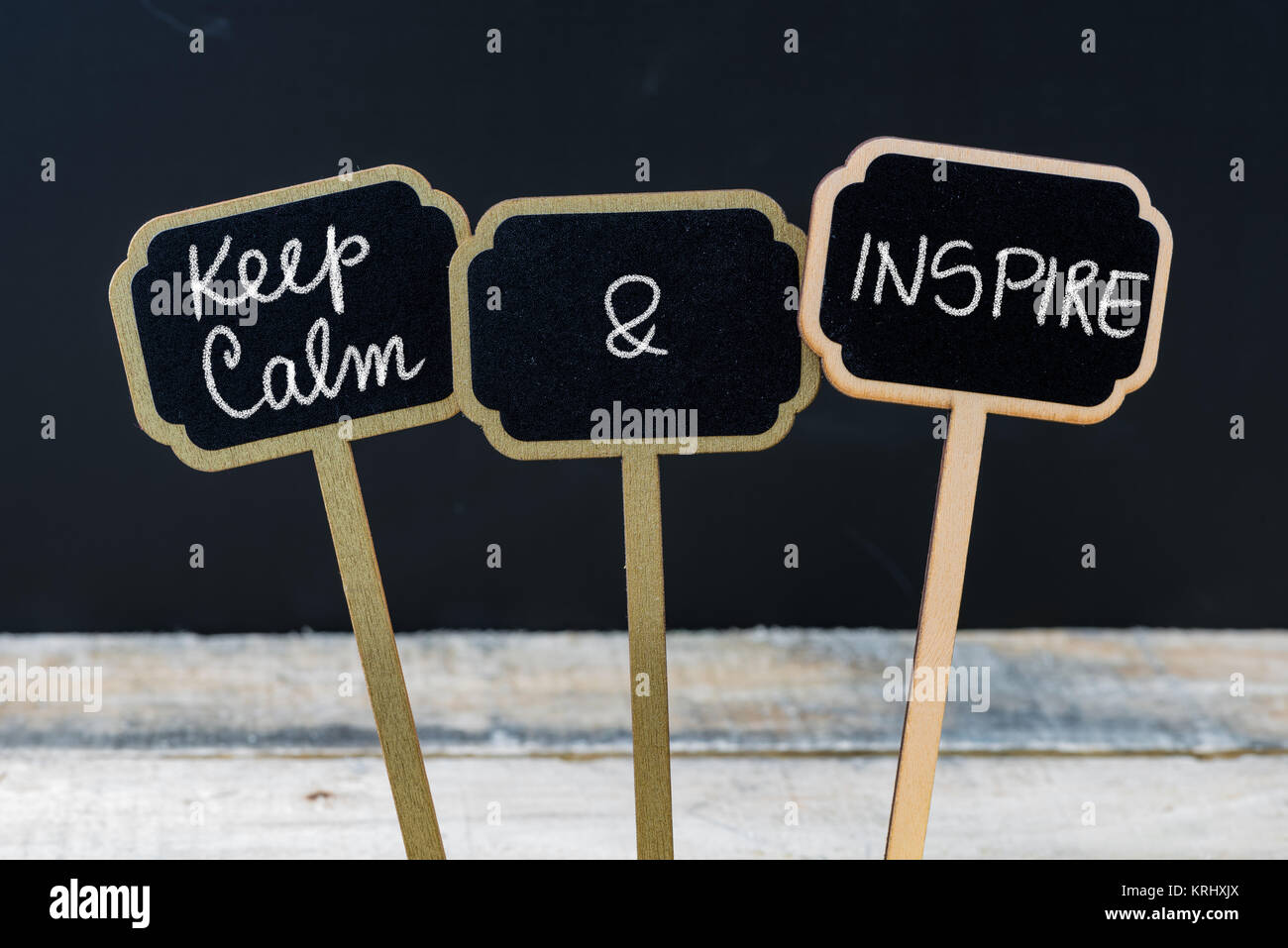 Keep Calm and Inspire message written with chalk on mini blackboard labels - Stock Image