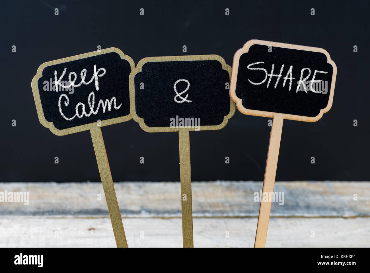 Keep Calm and Share message written with chalk on mini blackboard labels - Stock Image