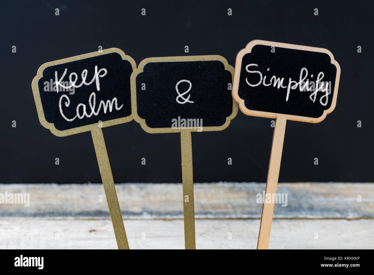 Keep Calm and Simplify message written with chalk on mini blackboard labels - Stock Image