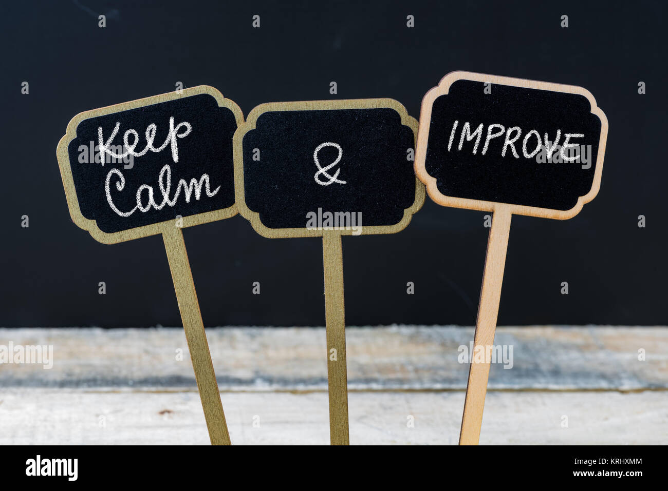 Keep Calm and Improve message written with chalk on mini blackboard labels - Stock Image