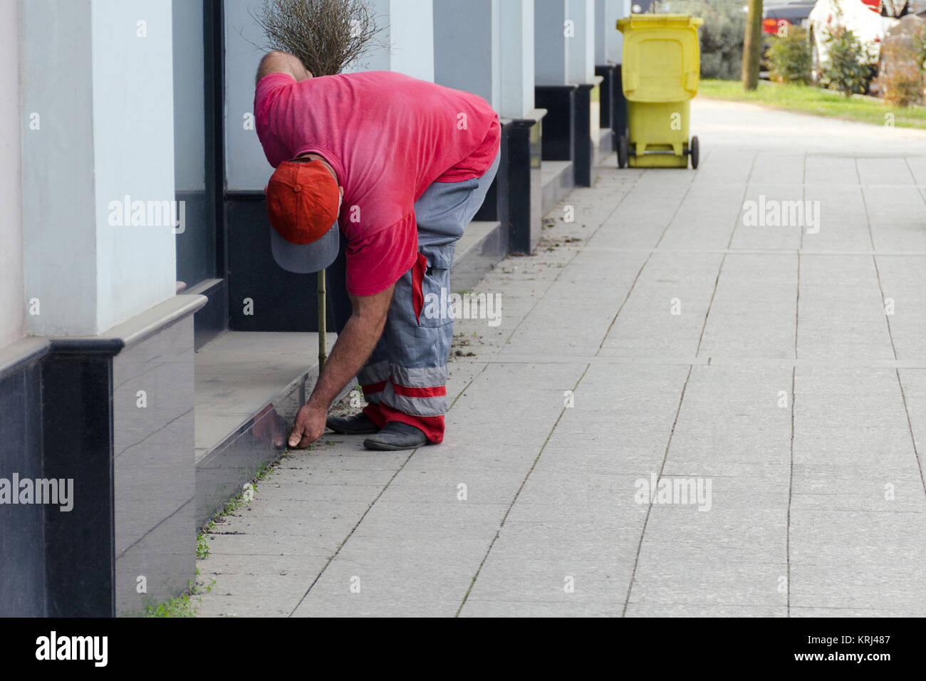 Cleaning of a city street - the worker the yard keeper in a uniform collects garbage by hands near a building, behind - Stock Image