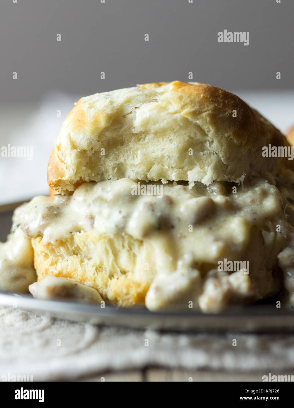 Biscuits with sausage gravy on a silver plate. - Stock Image