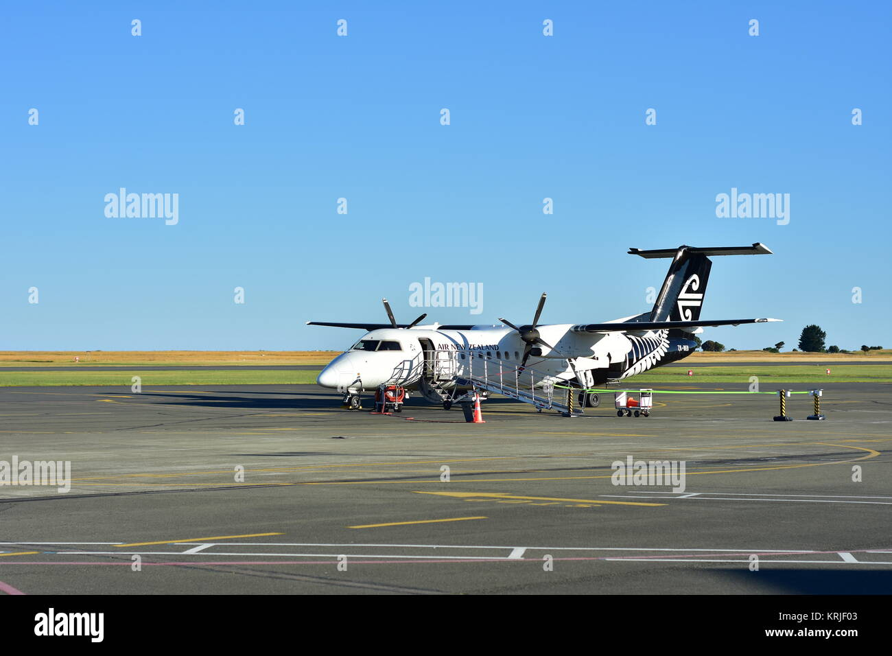 Turboprop twin engine plane in colors of  Air New Zealand parked on concrete airstrip. - Stock Image