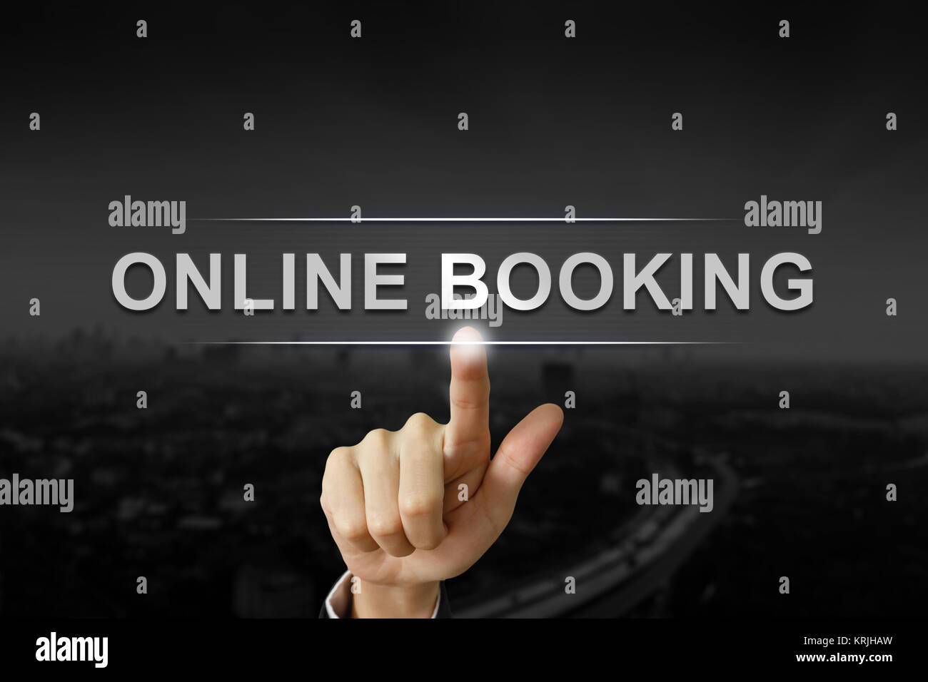 business hand pushing online booking button on black blurred background - Stock Image