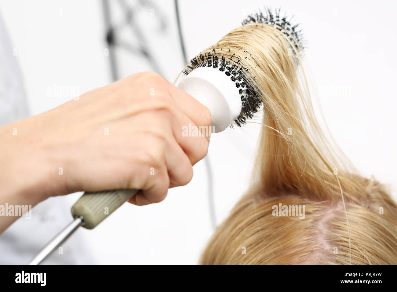 drying hair on a round brush - Stock Image