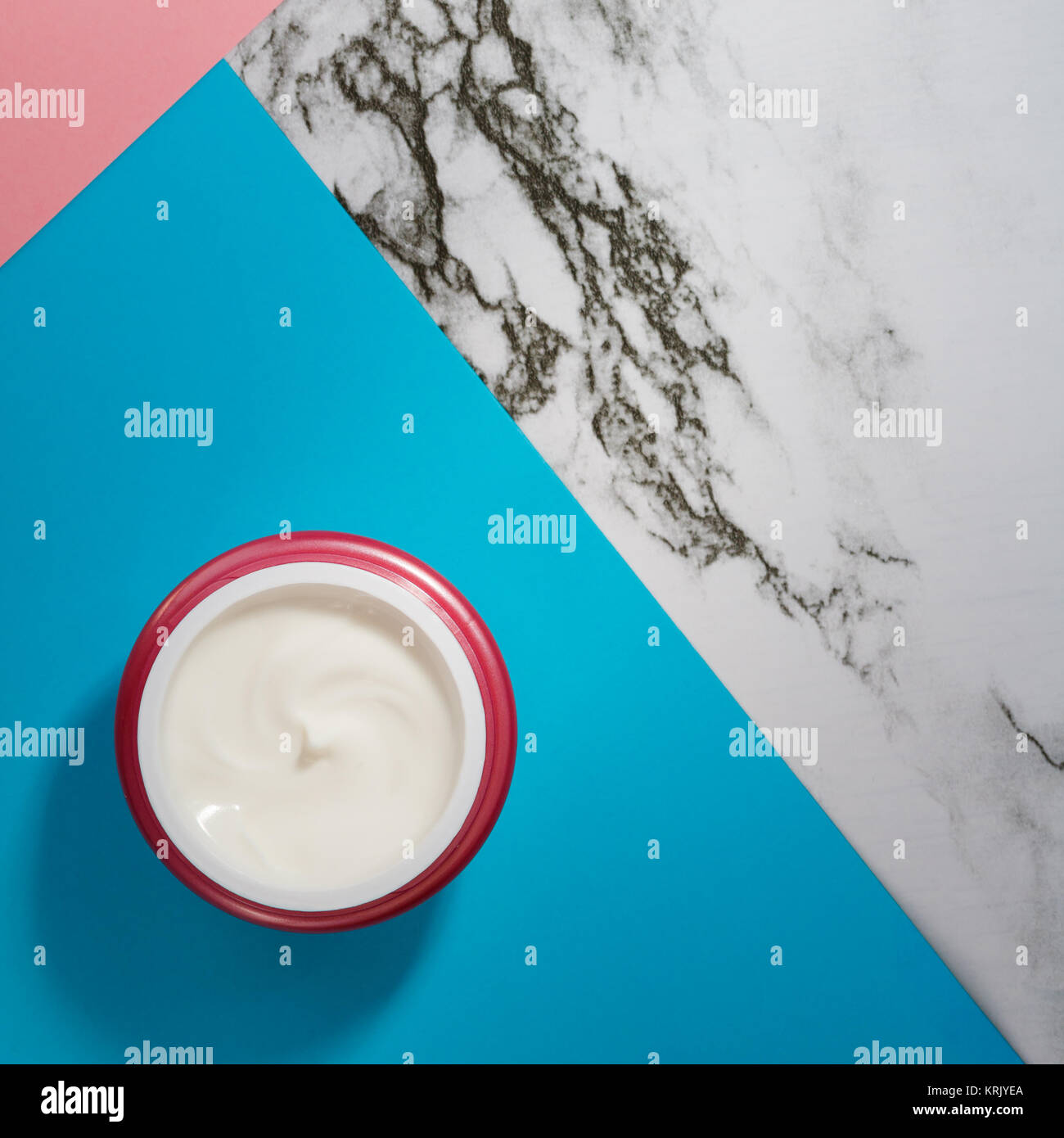 The white cream for skin in a pink container on a geometrical abstract colorful background. View from above. - Stock Image