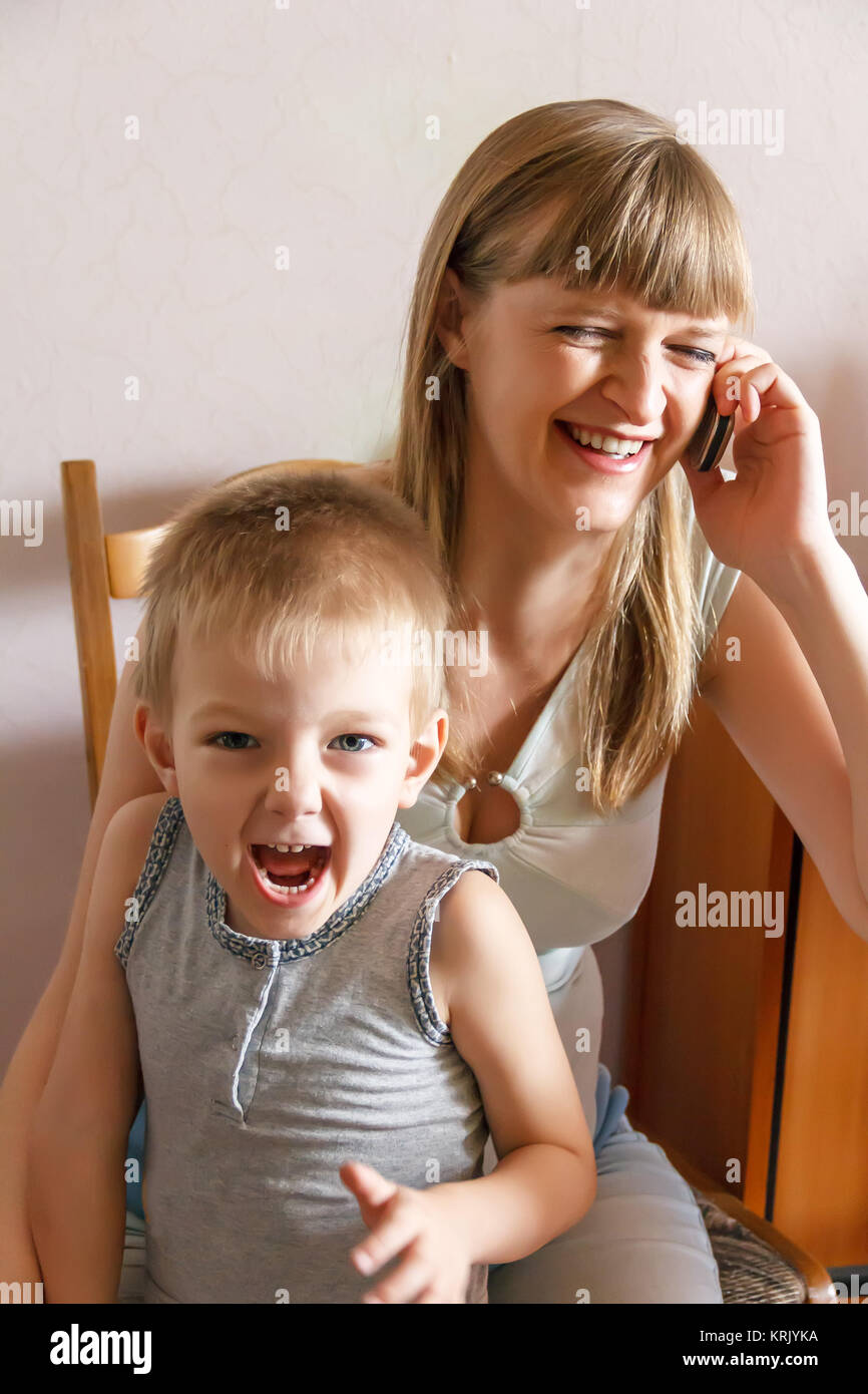 Screaming kid and mother with phone - Stock Image