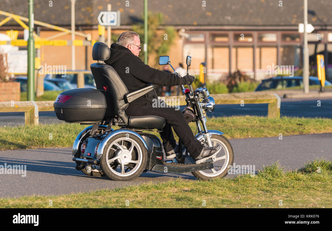 Man riding a 3 wheeled electric disabled mobility scooter in the UK. - Stock Image