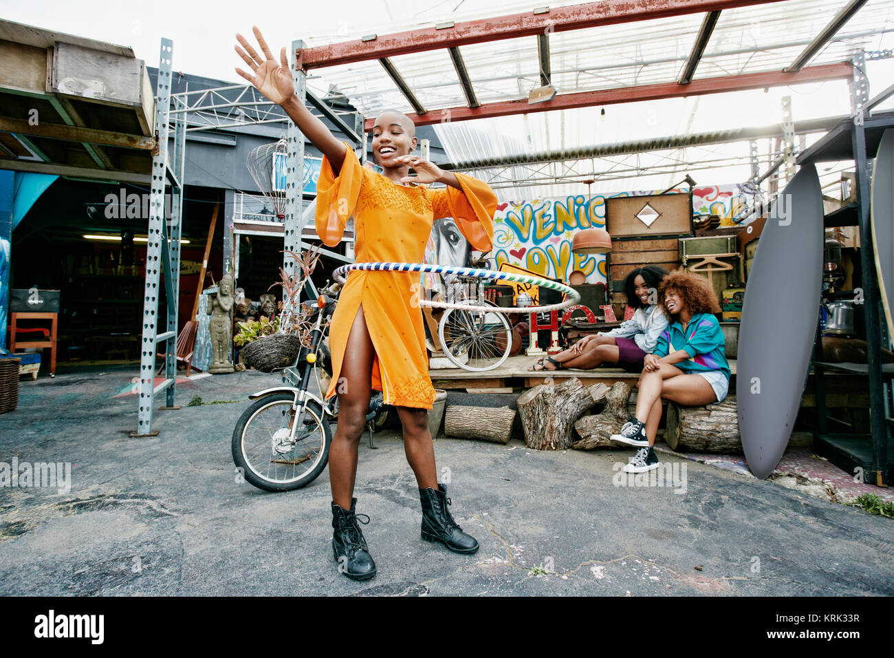 Friends watching woman spinning hoop around waist Stock Photo