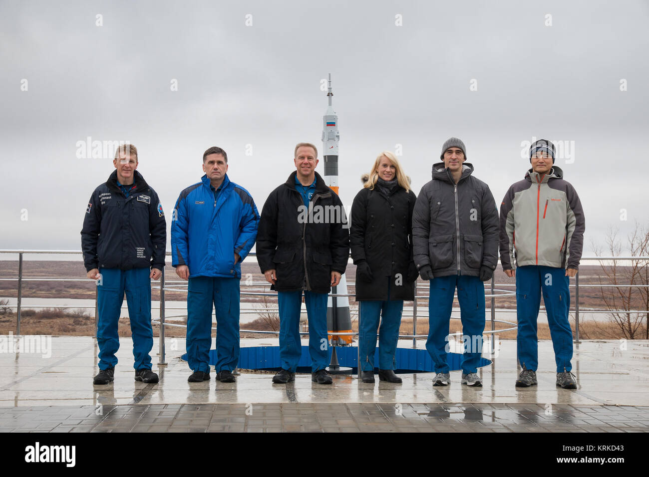 Soyuz TMA-19M crew and backup crew in front of a Soyuz rocket statue - Stock Image