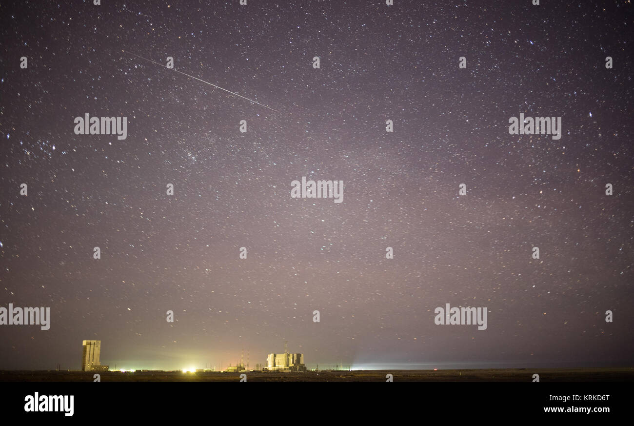 In this one minute exposure, a meteor streaks across the sky as the Soyuz TMA-19M spacecraft is rolled out by train - Stock Image