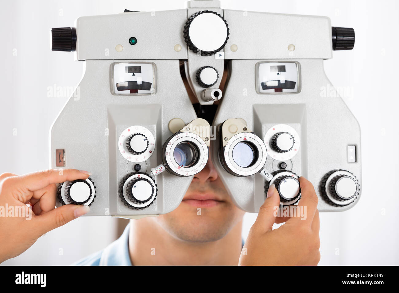 An Optometrist Adjusting Phoropter For Patient - Stock Image