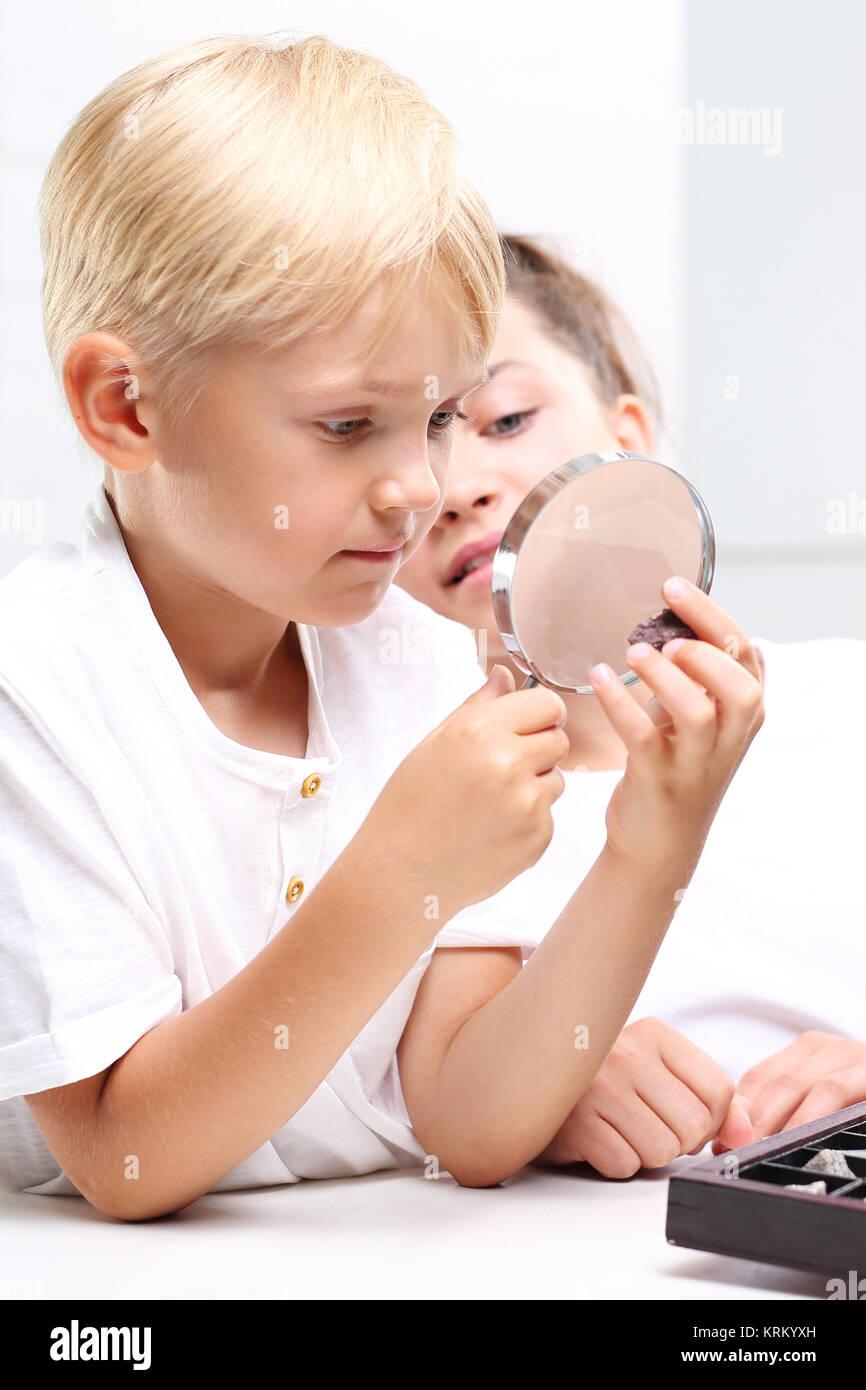 Dzieci oglądają minerały pod lupą - Stock Image