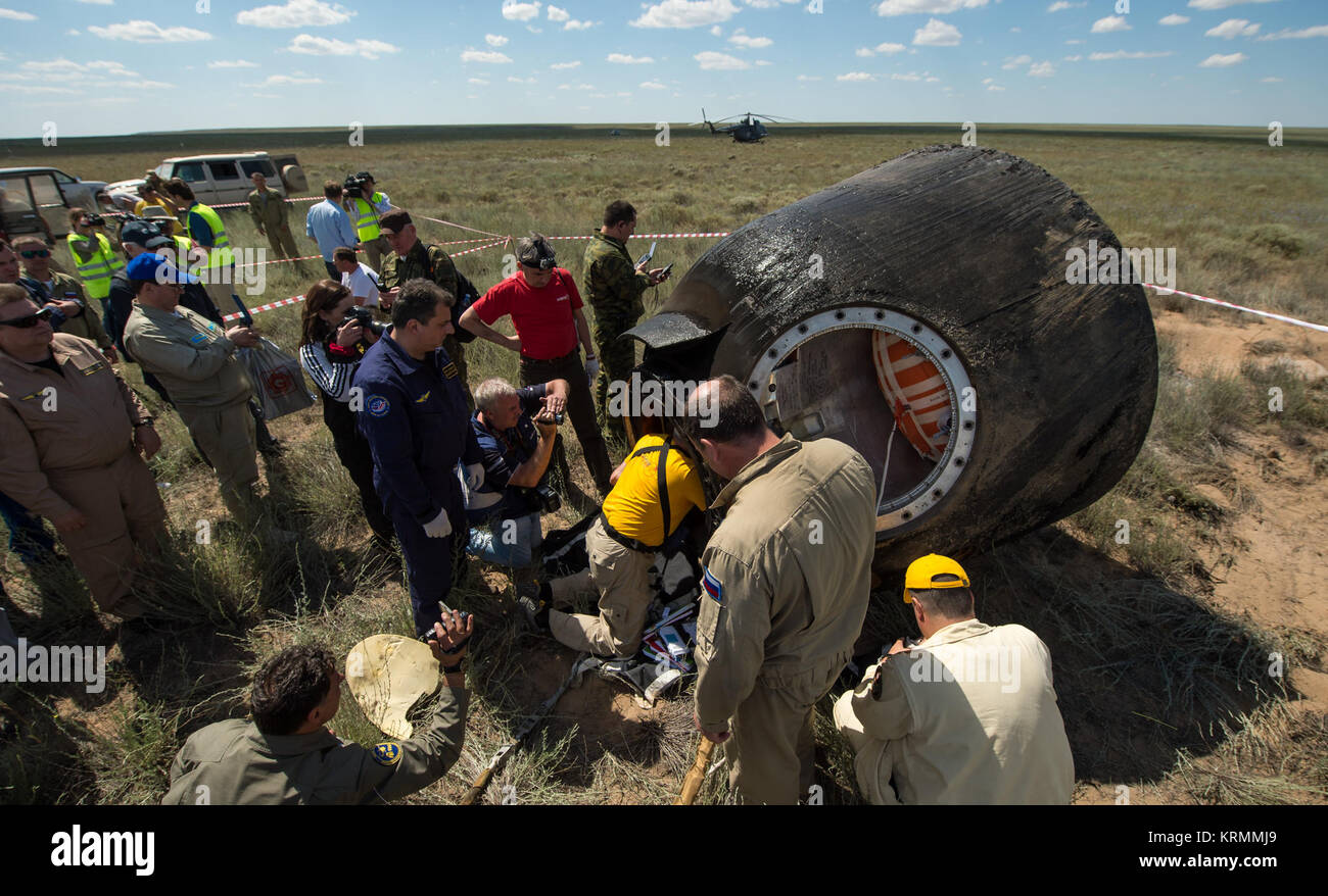 Russian support personnel work around the Soyuz TMA-19M spacecraft after it landed with Expedition 47 crew members - Stock Image