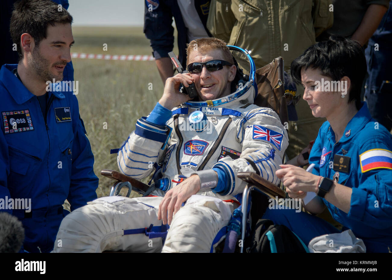 Tim Peake of the European Space Agency talks on a satellite phone in a chair outside the Soyuz TMA-19M spacecraft - Stock Image