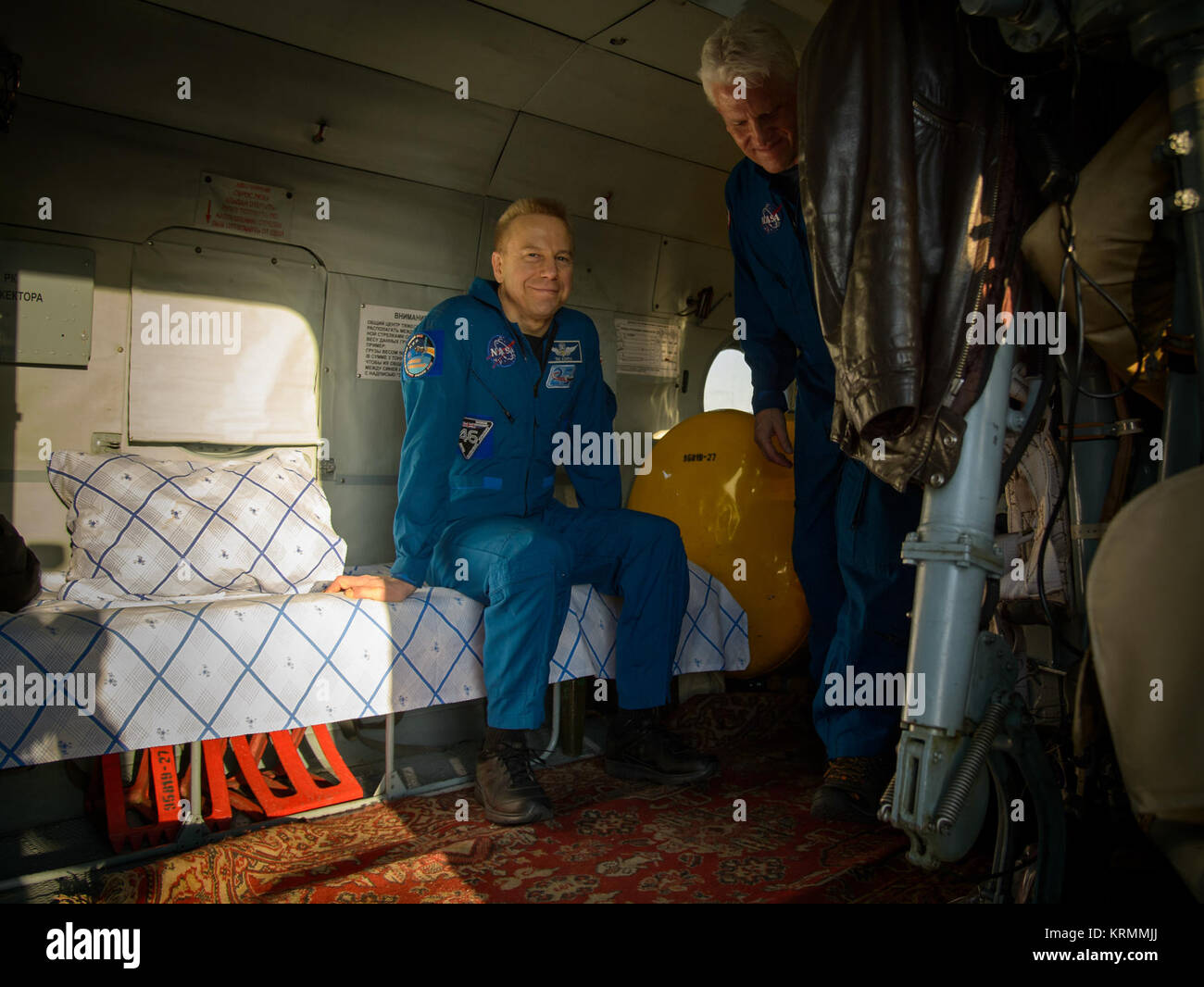 Expedition 47 astronaut Tim Kopra of NASA, left, and NASA Flight Surgeon Rainer Effenhauser are seen in the helicopter - Stock Image