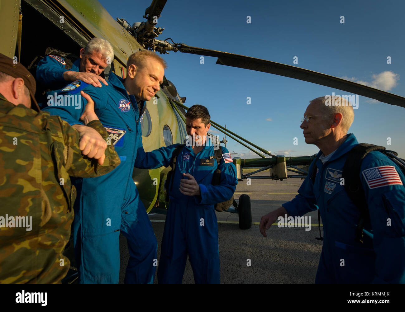Expedition 47 astronaut Tim Kopra of NASA is helped from the helicopter that brought him to the Karaganda Airport - Stock Image