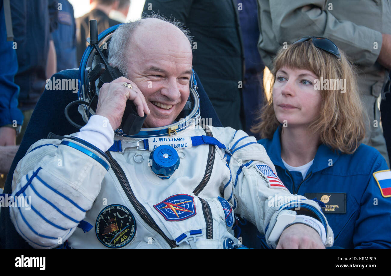 Expedition 48 NASA astronaut Jeff Williams rest in a chair and talks to his family on a satellite phone outside Stock Photo