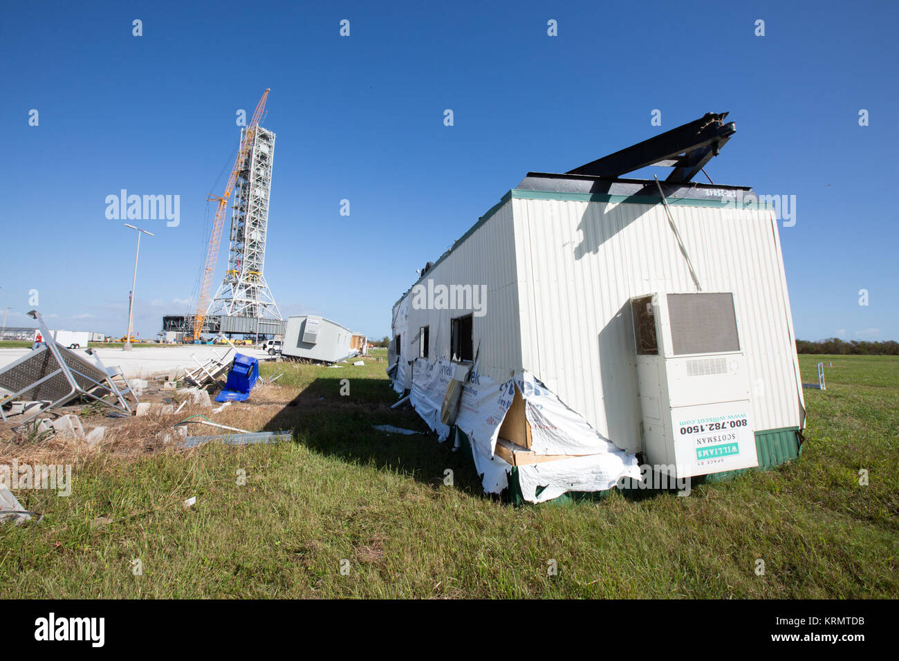 A damaged construction trailer and several pieces of associated debris, aftermath of Hurricane Matthew, are seen - Stock Image