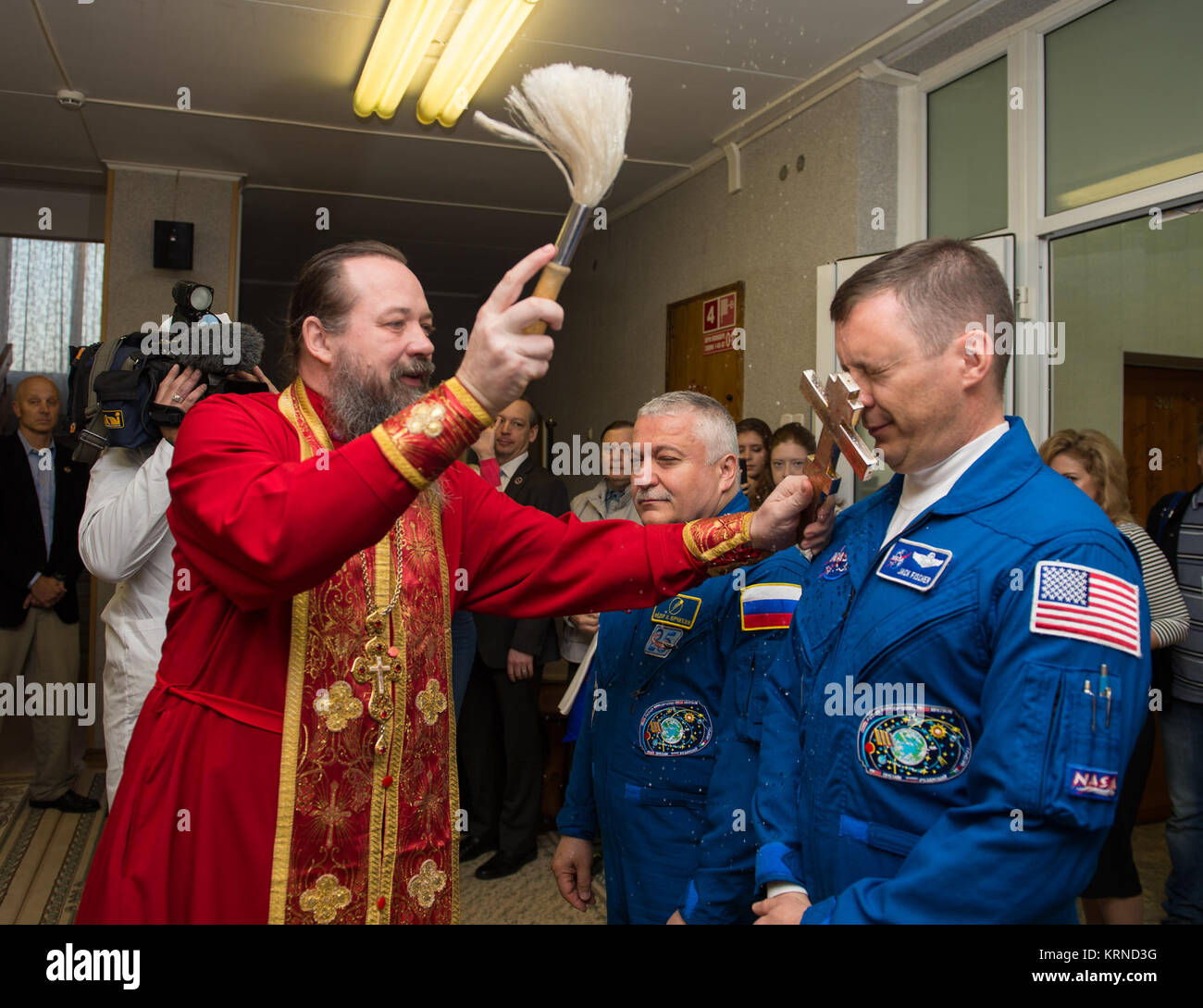 Expedition 51 Flight Engineer Jack Fischer of NASA, right, receives the traditional blessing from a Russian Orthodox - Stock Image