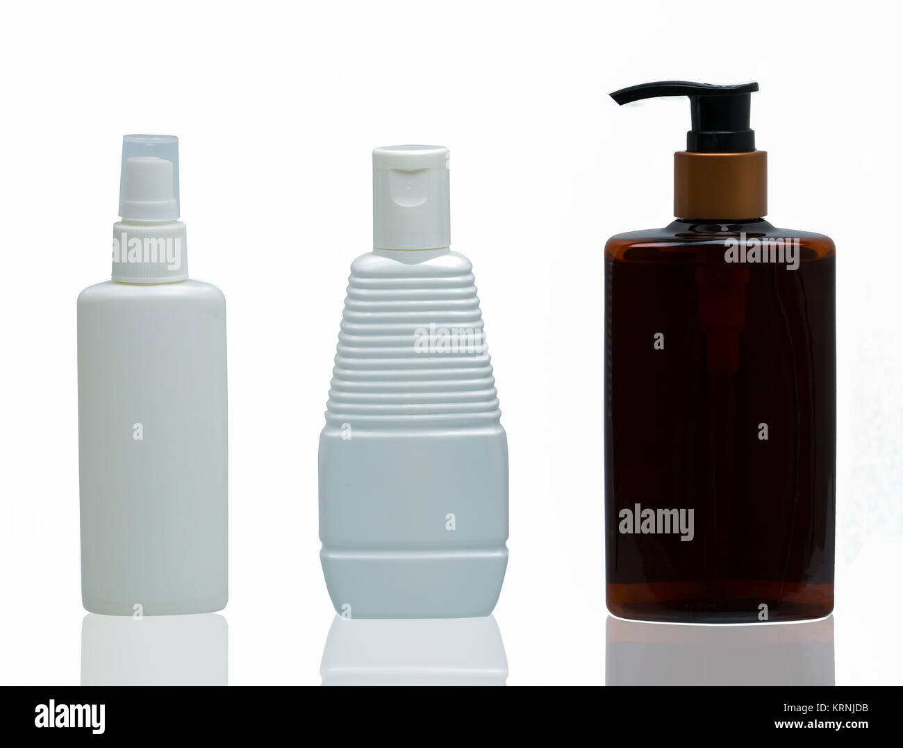 Three white and brown plastic cosmetic bottles with different type of cap : pump, spray and cap isolated on the Stock Photo