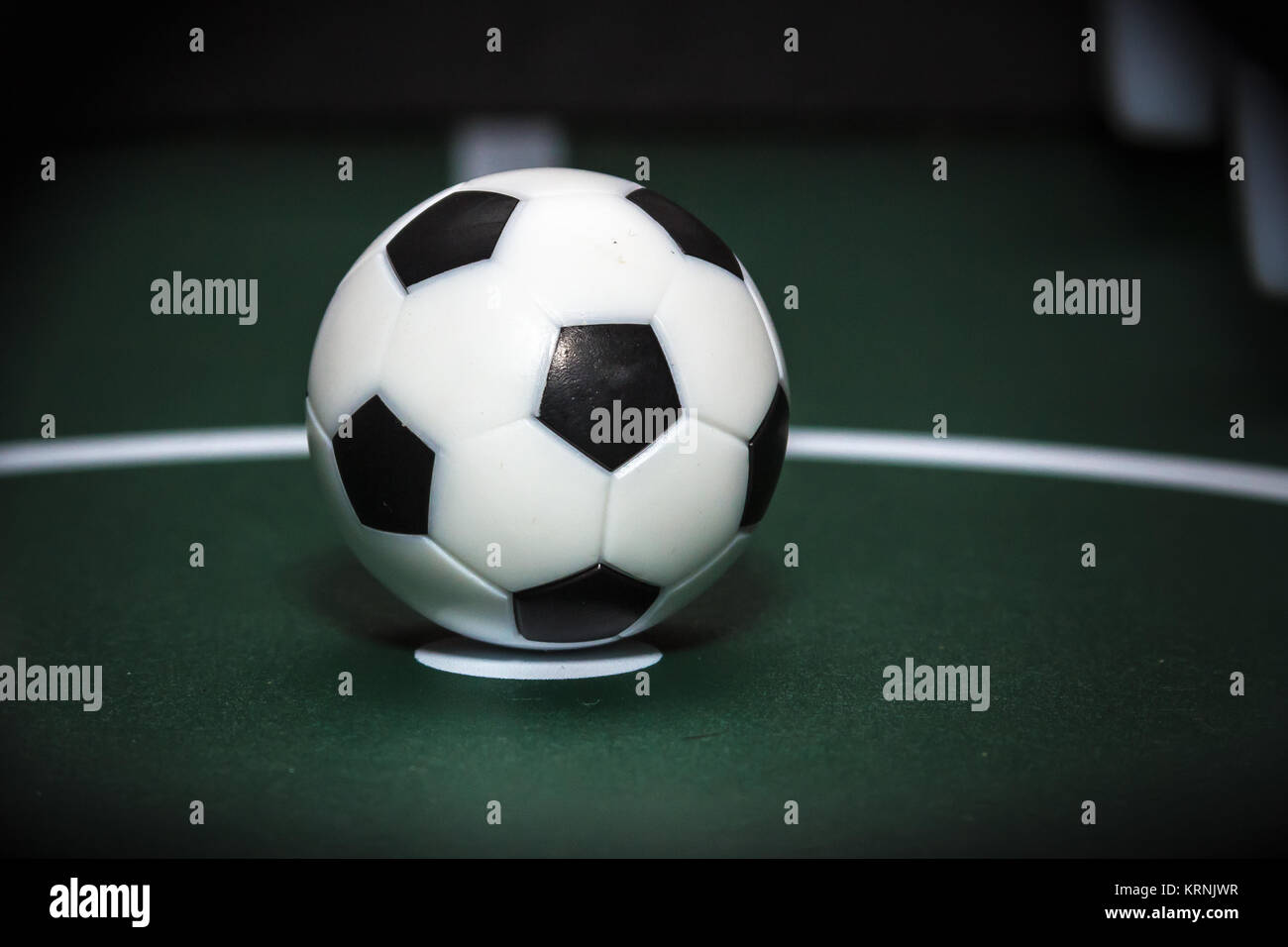 Soccer table game. Green field and plastic ball on it. Sport background - Stock Image