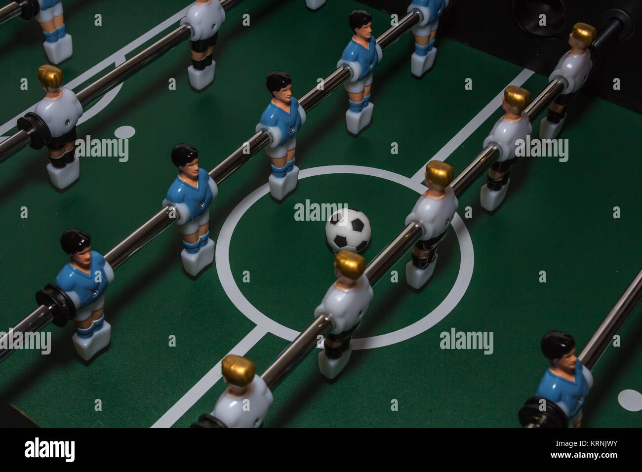 Soccer table game. Green field with blue and white plastic footballers. Sport background - Stock Image