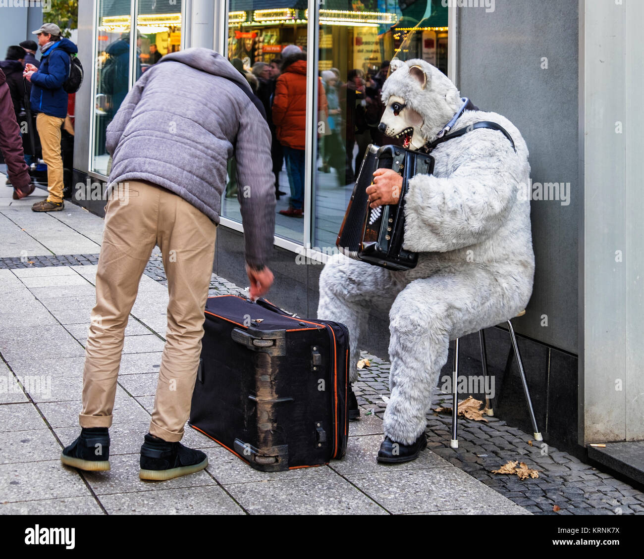 Frankfurt, Germany.Passerby giving money to man playing accorcdion in Bear fancy dress outfit - Stock Image