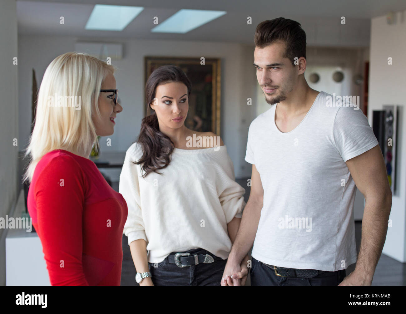 Girlfriend shocked on disloyal boyfriend flirting with woman in red dress, indoors - Stock Image