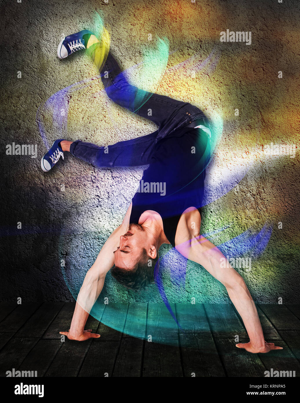 Break dancer doing handstand against colorful wall background - Stock Photo