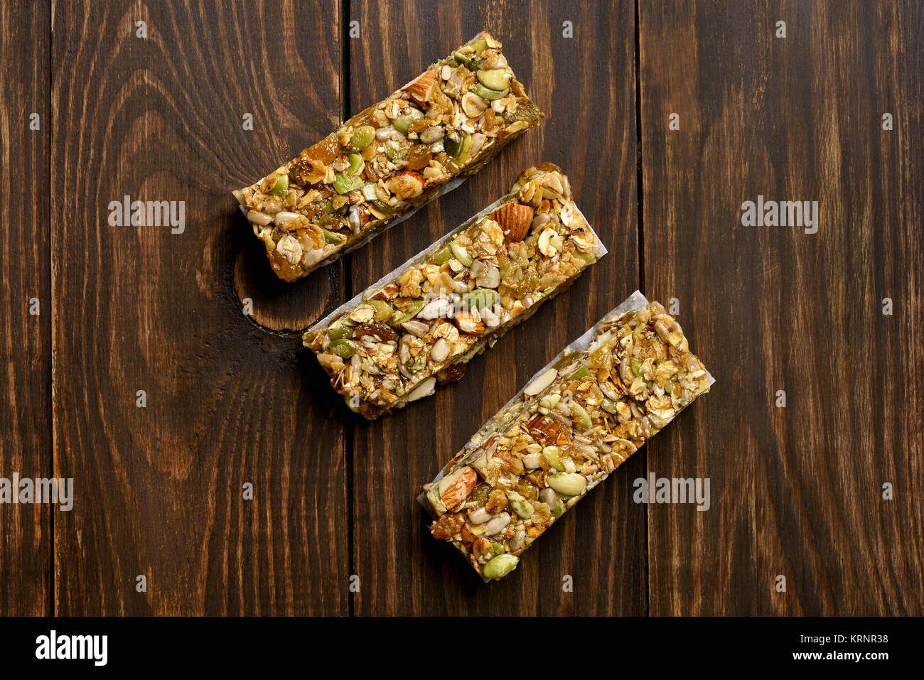 Granola bar. Energy snack on wooden background. Top view, flat lay - Stock Image