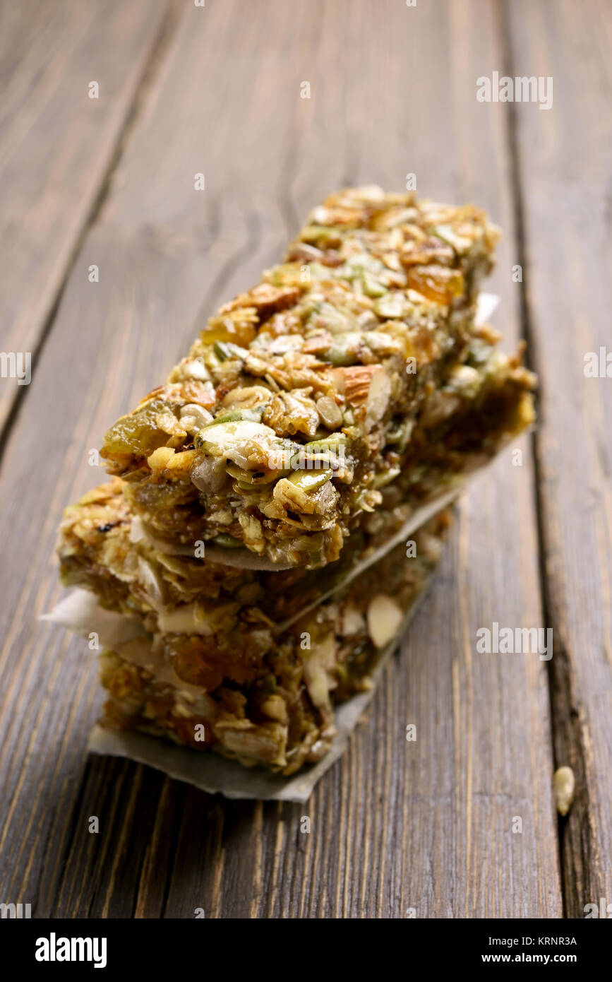 Stacked no baked granola bar. Healthy energy snack on wooden background. Shallow depth of field - Stock Image
