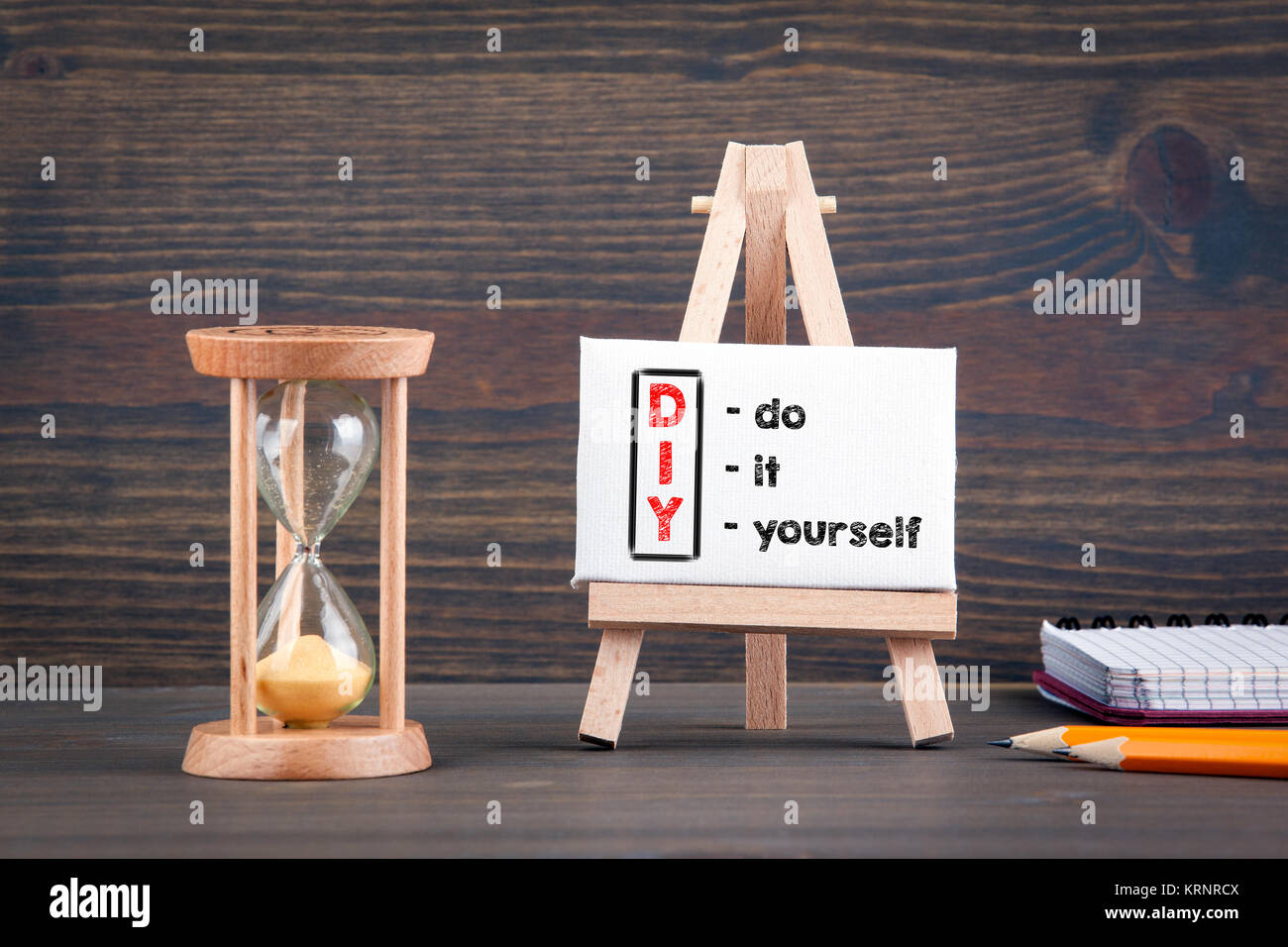 DIY do it yourself. Sandglass, hourglass or egg timer on wooden table - Stock Image