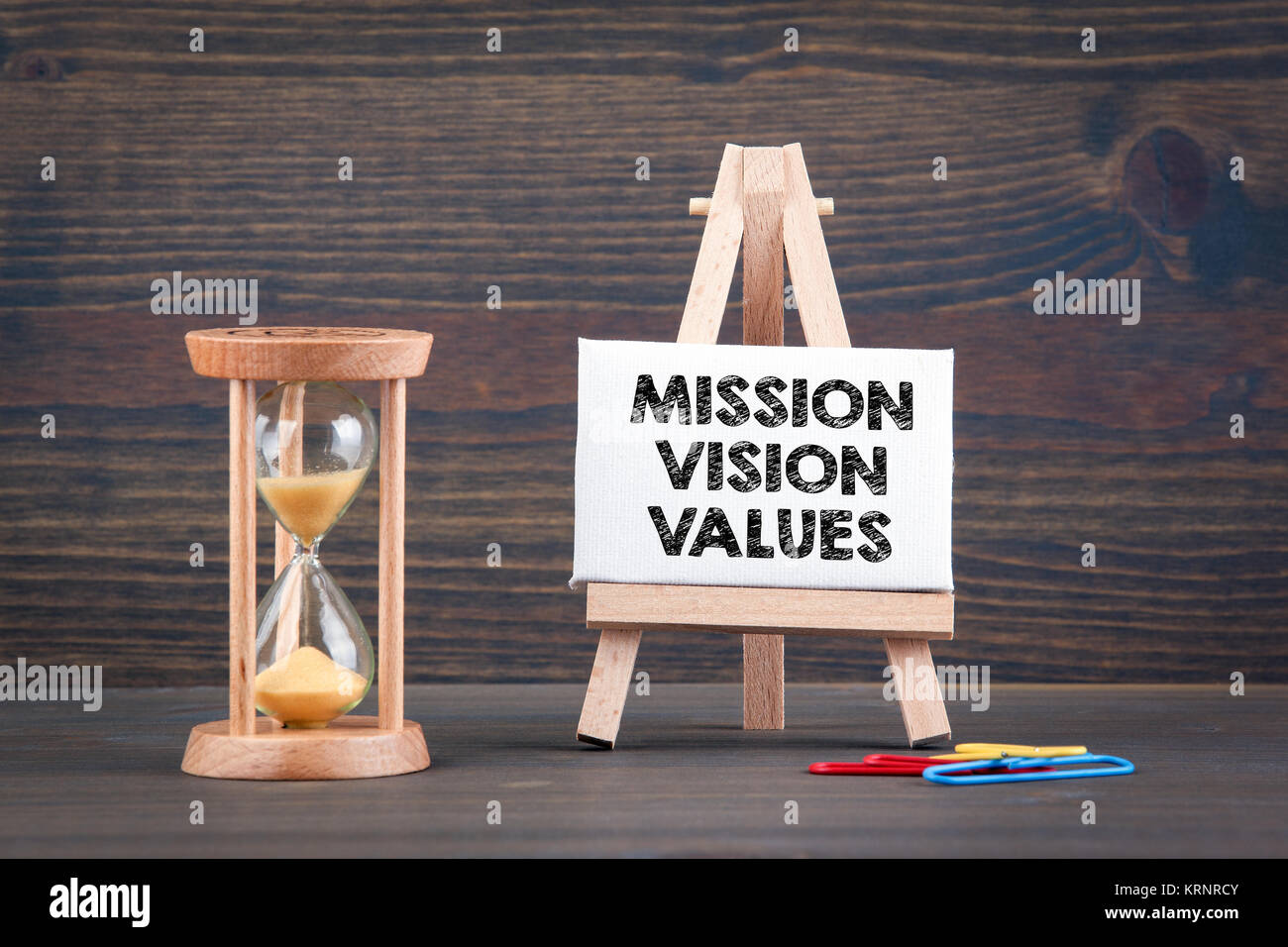 Mission, Vision and Values. Sandglass, hourglass or egg timer on wooden table  - Stock Image