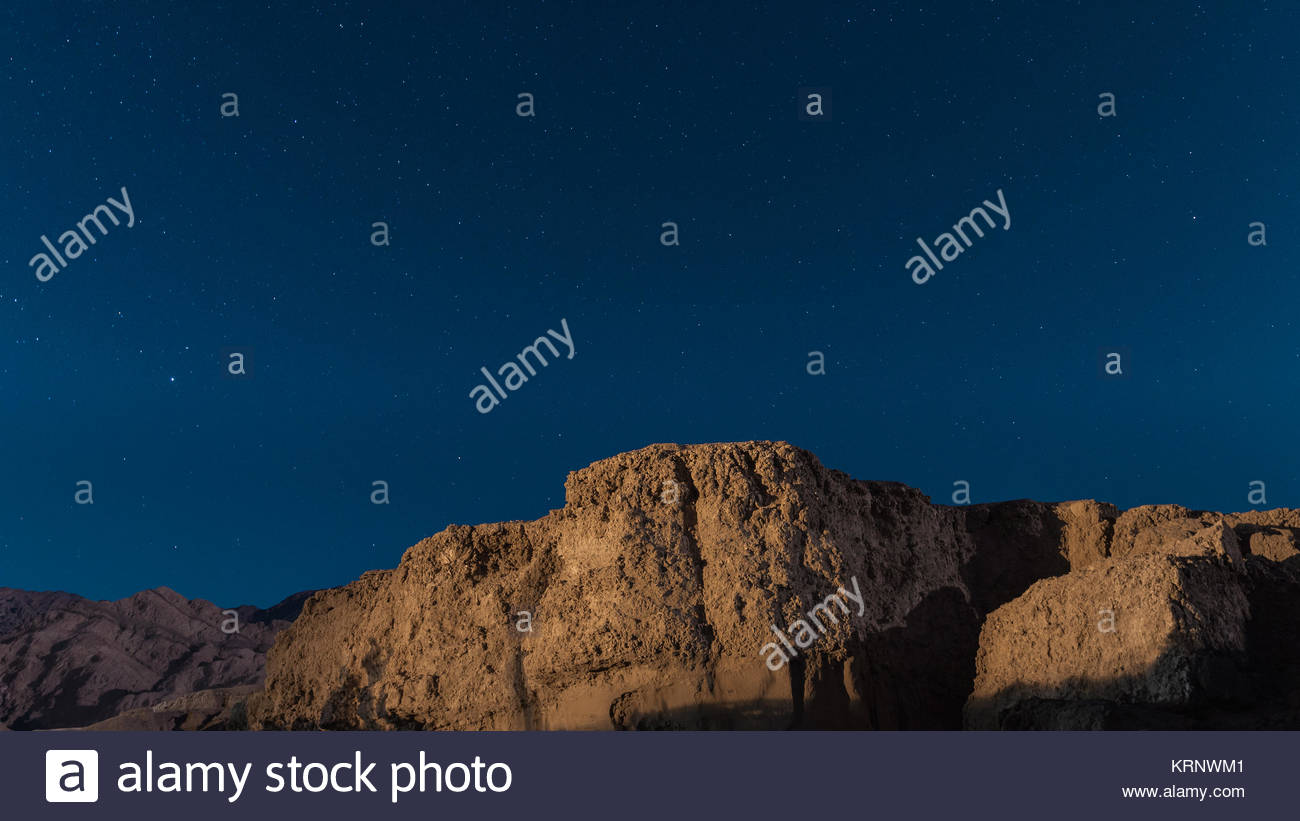 Edgy mountain hugging the blue sky with bright stars - Stock Image