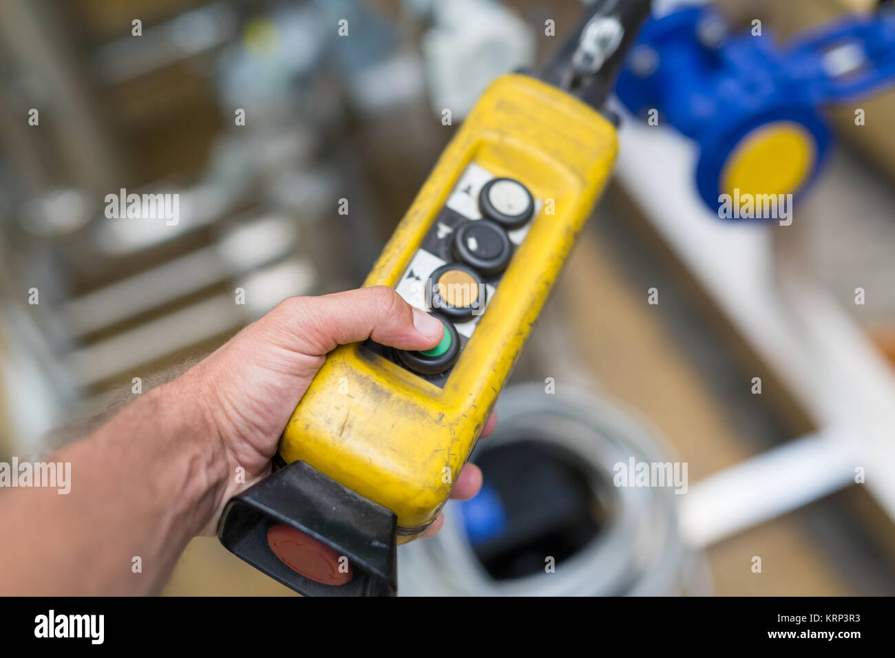 Industrial worker pushing on button of machinery controler. - Stock Image