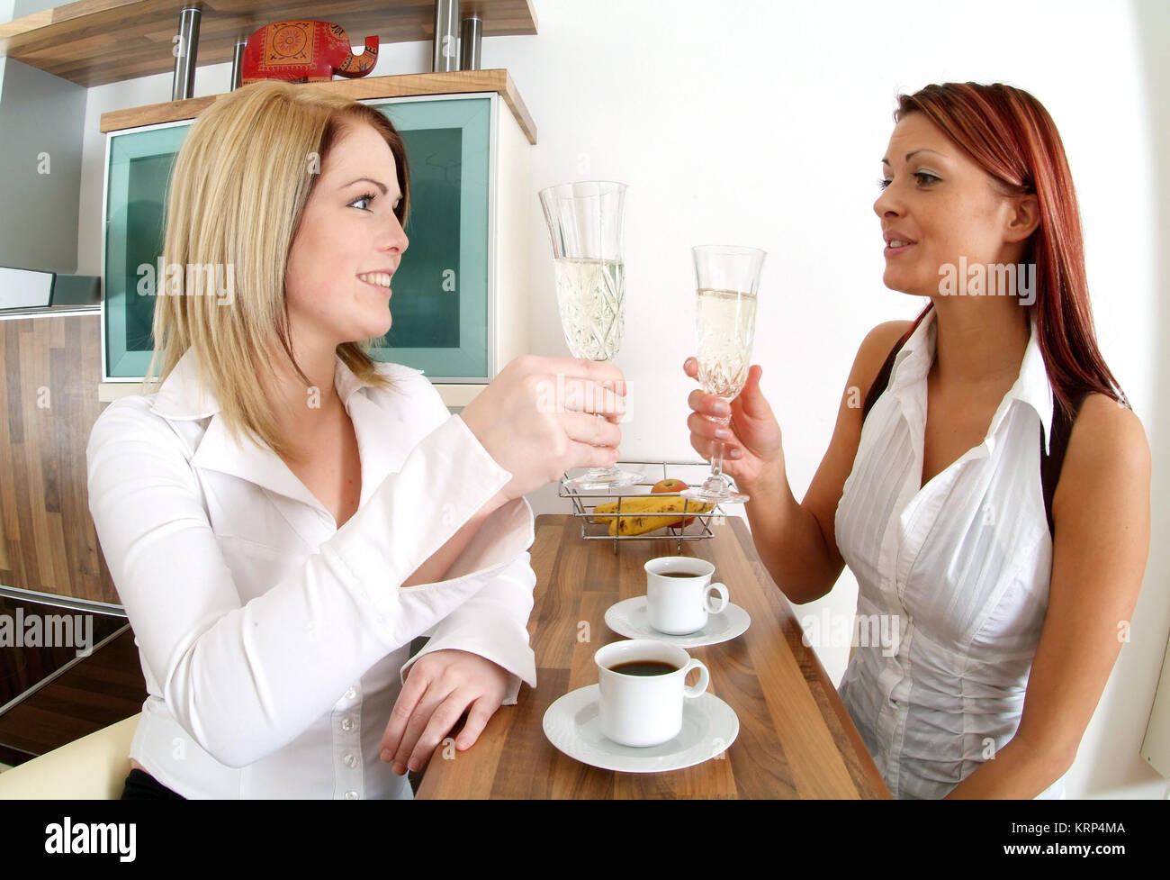 Zwei junge Frauen trinken gemeinsam Sekt an der Kuechenbar - two young women drinking sparkling wine - Stock Image