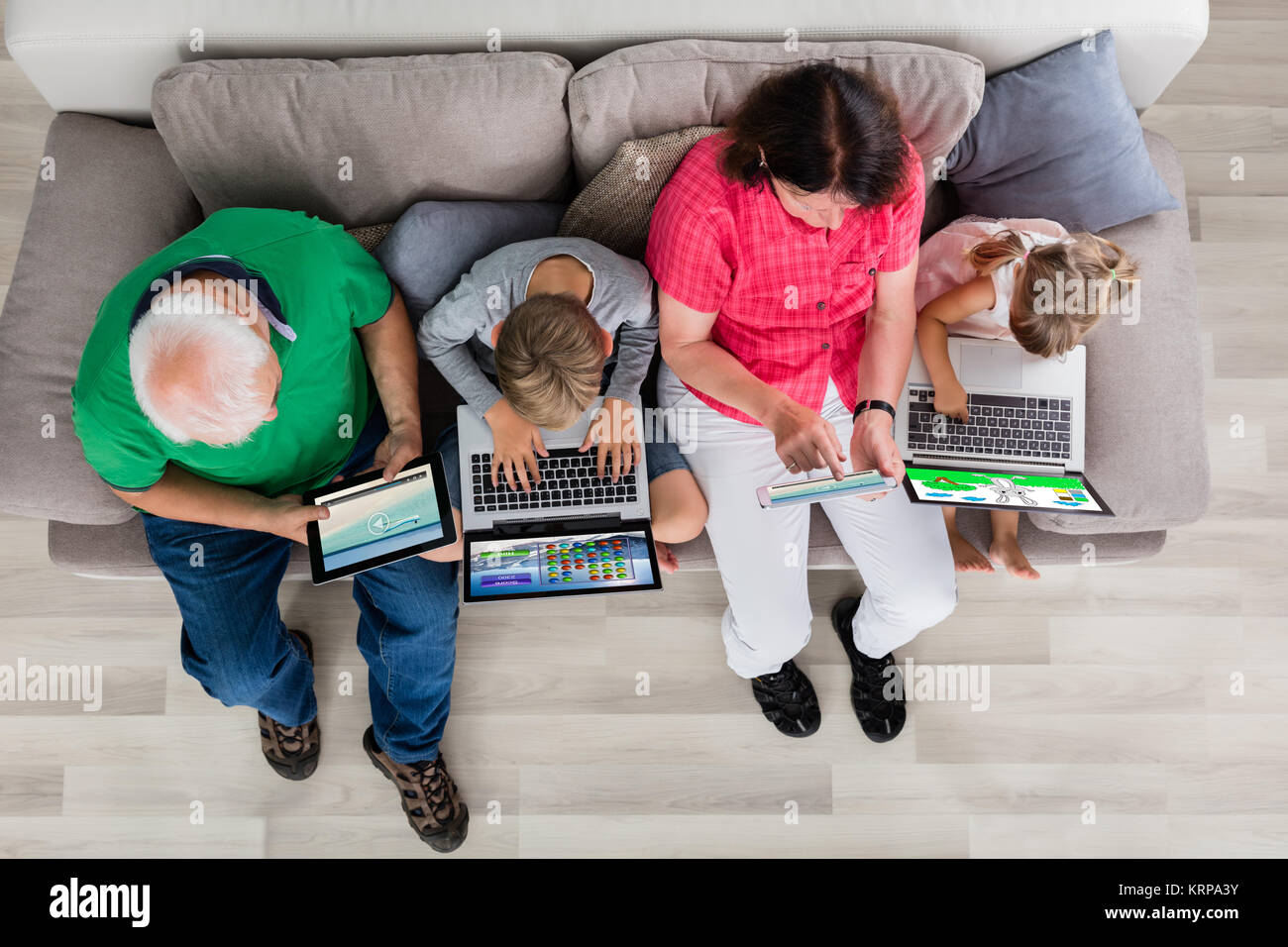Family With Their Laptop And Digital Tablet At Home - Stock Image