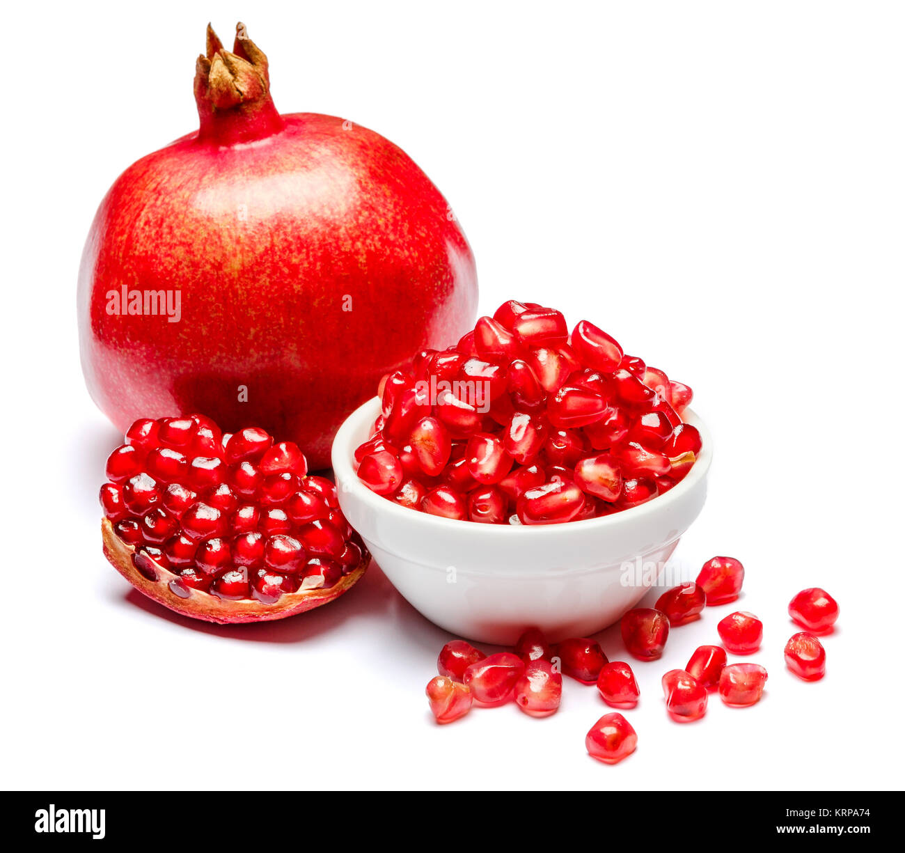 Pomegranate and seeds in ceramic bowl close-up - Stock Image